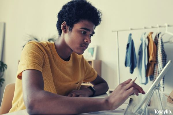 man in yellow crew neck t shirt while using tablet hanging clothes on the background