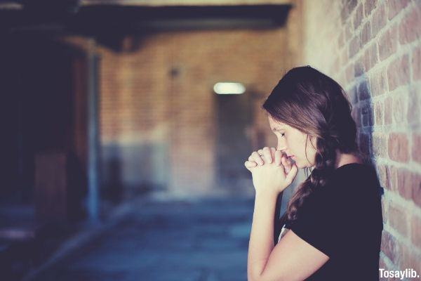 woman in black shirt praying while leaning on the brick wall