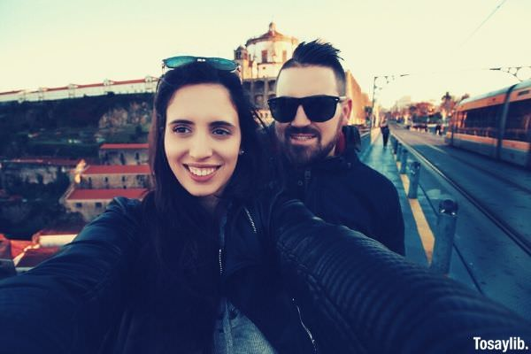 travelling couple love smiling selfie wearing black jackets with sunglasses