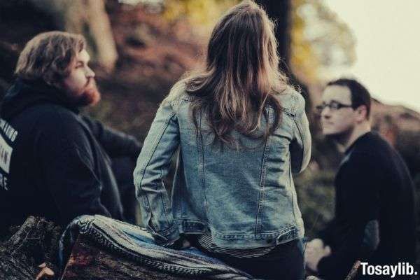 woman in gray jacket talking with to guys in black rehab