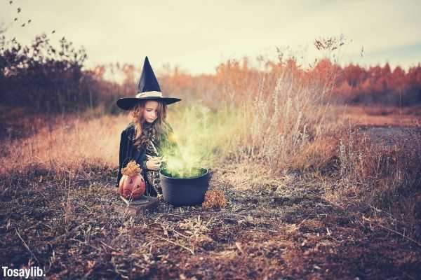 Girl in witch costume sitting on dried field