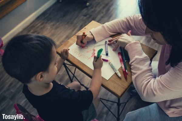 boy boy in black shirt writing with green pen mother in pink long sleeves writing using color