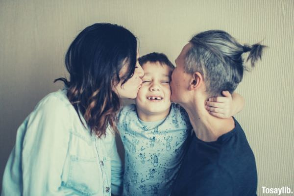man in black and woman in denim shirt kissing their son