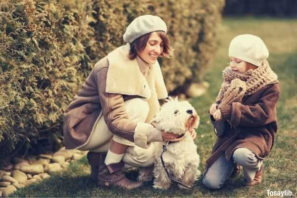 mother and daughter playing with their dog happy cold weather coat garden