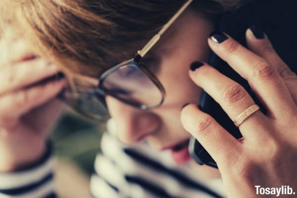 thoughtful female speaking on smartphone while working remotely eyeglasses ring touching her hair