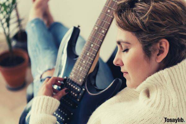 brown haired woman playing electric guitar with emotions