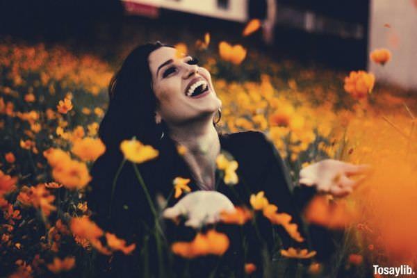 woman wearing black blouse laughing in orange yellow flower field