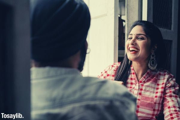 trendy young woman with dangling earrings laughing at joke told by man