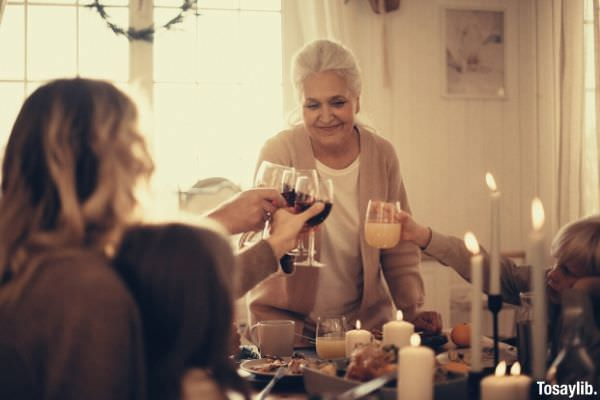 woman on gray cardigan standing near table doing cheers smiling happy