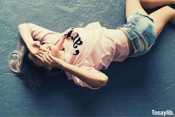 woman wearing pink printed crew neck t shirt and blue faded denim shorts lying on the floor