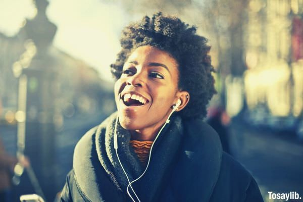 close up photo of curly haired woman listening to music smiling