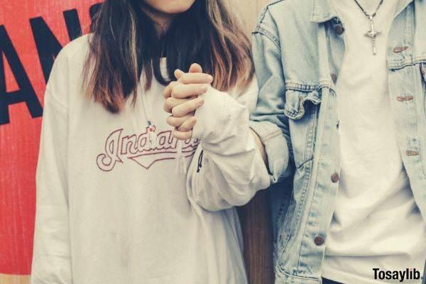 woman holding mans hand wearing denim jacket