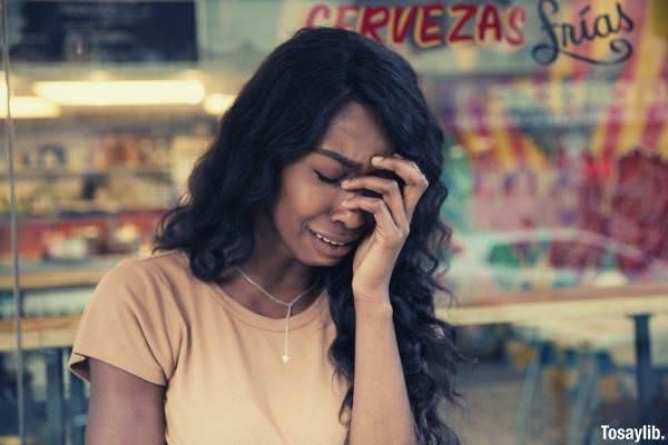 black woman crying wearing necklace and beige shirt
