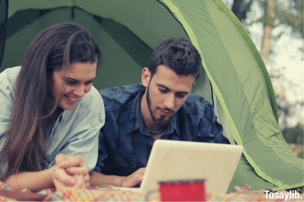 young couple browsing netbook at campsite outside the tent