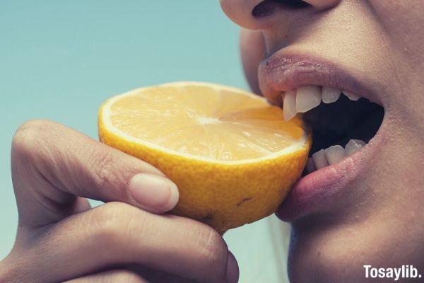 woman biting lemon fruit teeth hand