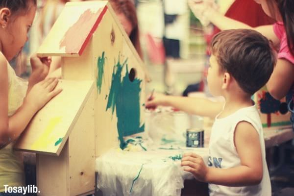 boy in white tank top holding blue green paint painting a bird house with another kids