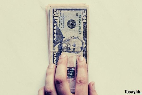 hand holding fifty dollar bank notes on white surface