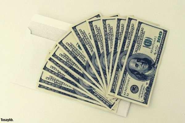 many money one hundred dollar bills white envelope