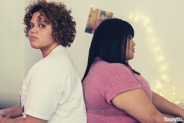 two unhappy woman wearing white and pink shirt fat inside the room with lights