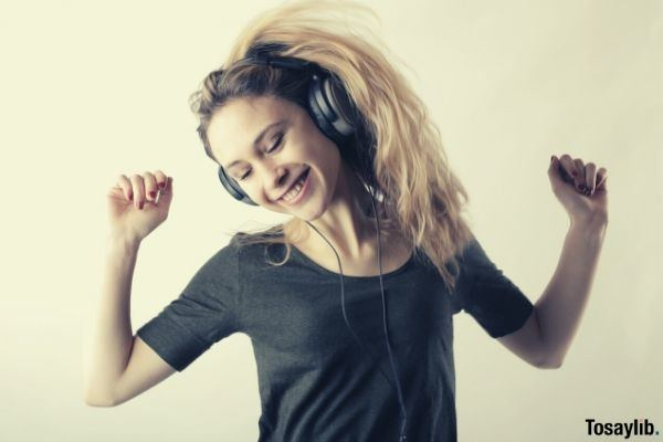 woman in gray shirt dancing banging her hair while listening to her headphones
