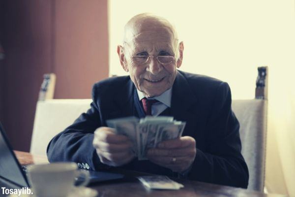 happy senior businessman wearing eyeglasses counting money while sitting at table with laptop