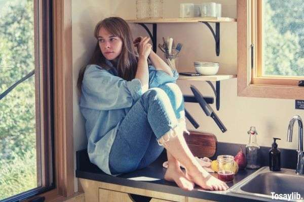 sad woman sitting on kitchen counter near sink and looking away