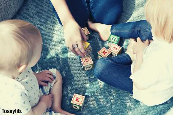 two blonde haired toddlers playing letter cubes with their mom