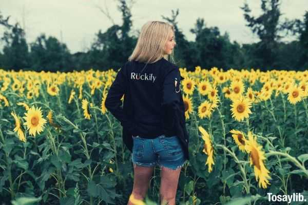 woman in black sweater standing on the sunflower field