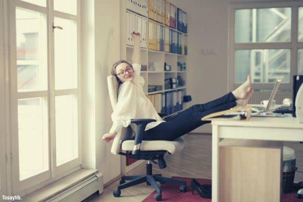 dreamy female employee relaxing with feet on table in office stretching wearing white top files on cabinet