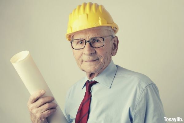 old man in engineer hat and formal attire holding a paper