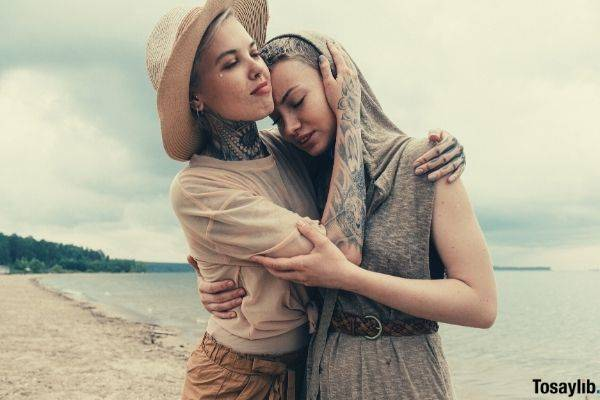 woman with lots of tattoo and wearing hat comforting her friend in sleeveless hoodie