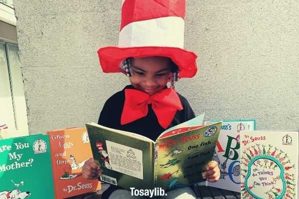 girl in black shirt wearing red and white hat holding Dr Seuss book while sitting on the table