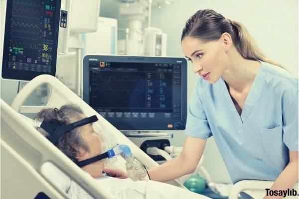 old-woman-with-oxygen-lied-down-on-bed-nurse-talking-with-her