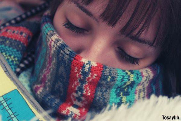 woman tired resting eyes closed eyelashes red bangs knitted colorful scarf