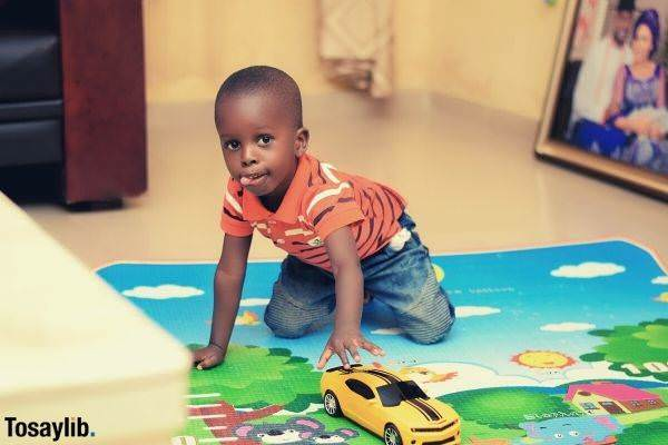 cute boy wearing orange stripes playing a chevy camaro toy car on the floor