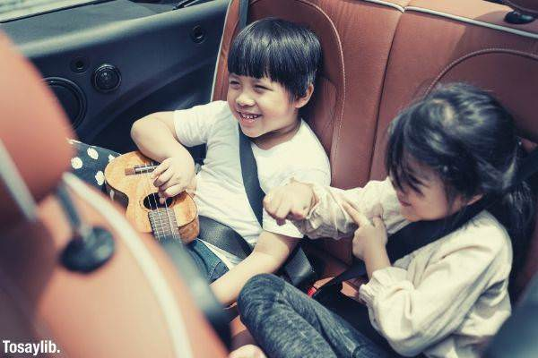 two happy asian traveling in the car boy holding ukulele
