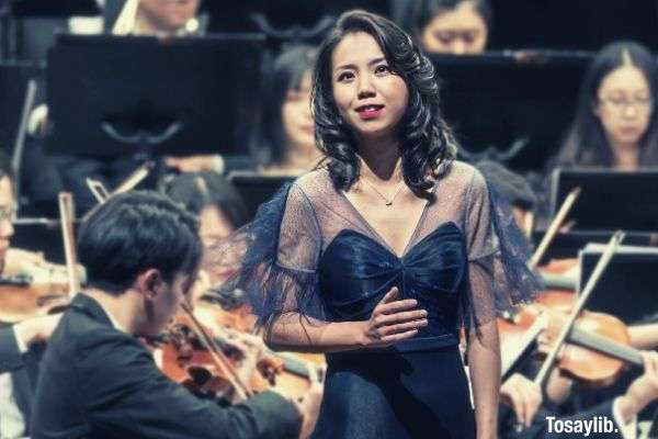 woman in formal dress in front of orchestral band