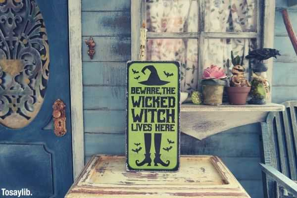 blue yellow wooden wall beware the wicked witch lives here signage