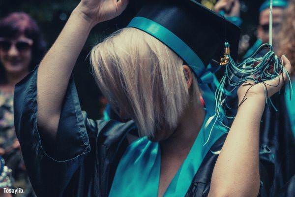 woman wearing blue and black graduation coat blonde hair