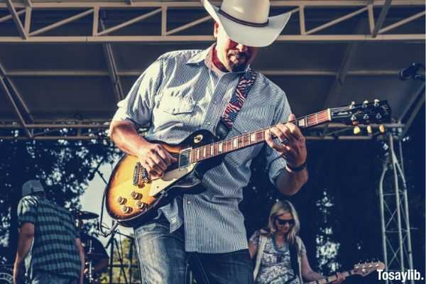 man in white and blue pinstripped button up long sleeves polo and cowboy hat playing guitar on stage