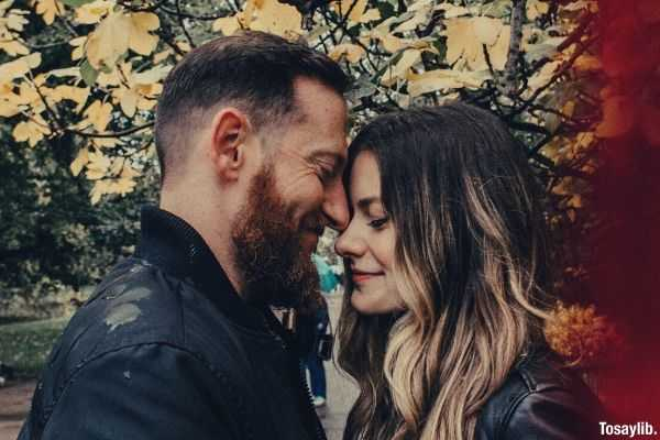 happy couple in black leather jacket under a tree