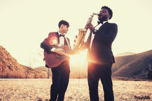 two men playing saxophone and guitar on a dried field during sunset