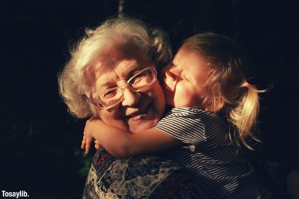 little girl in black and white stripes hugging old woman in blouse with white hair smiling