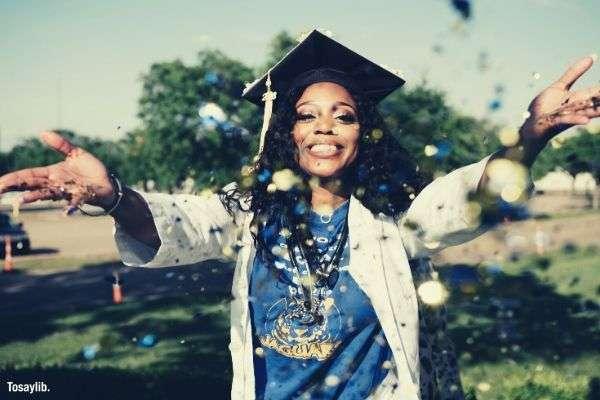graduate blue shirt white gown black girl throwing confetti