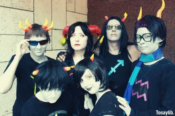 group of people wearing black halloween costumes group photo near concrete wall