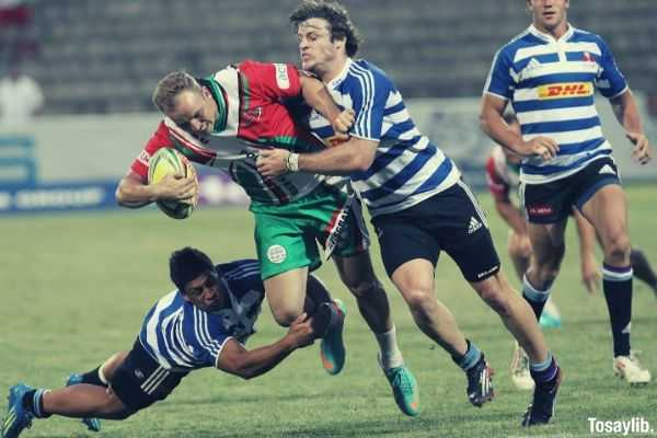 man in blue and white striped soccer jersey playing rugby two people pulling him