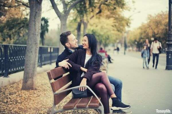 couple sitting on wooden bench looking at each other park people