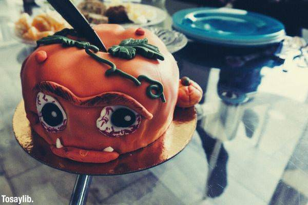 orange covered cake pumpkin themed on the table being sliced