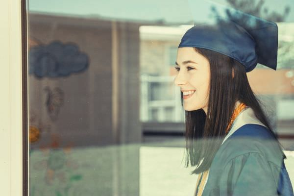 woman-in-blue-feature-academic-gown-smiling-looking-outside-the-window