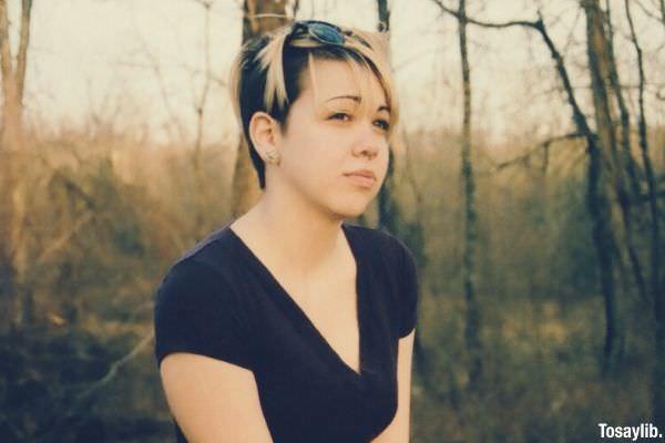 01 woman sad wearing black blonde hair sitting on a lying tree trunk